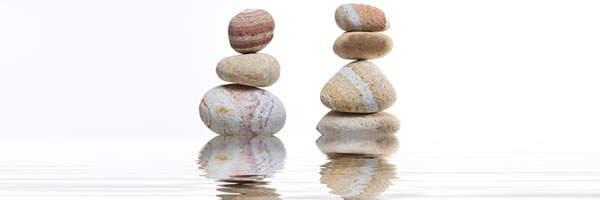 two stacks of balanced stones with reflection in water
