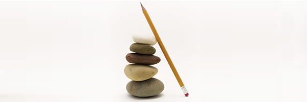 A pencil leaning against stack of balanced stones