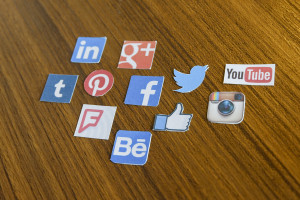 Small tiles with the different social media platform logos on a wooden table