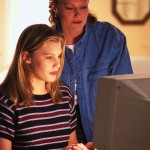 A mother watches her teenage daughter work on the computer.